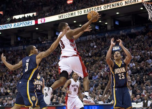Toronto Raptors guard Kyle Lowry, centre, drives the net past Indiana Pacers guard George Hill, left, and Pacers forward Gerald Green, right, during first half NBA basketball action in Toronto on Wednesday, Oct. 31, 2012. (AP Photo/The Canadian Press, Nathan Denette)