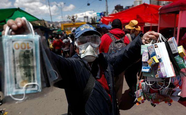 PHOTO: A man wearing a mask and goggles amid the coronavirus pandemic sells masks decorated with fake money at the annual Alasita Fair in La Paz, Bolivia, on March 24, 2021. (Juan Karita/AP)