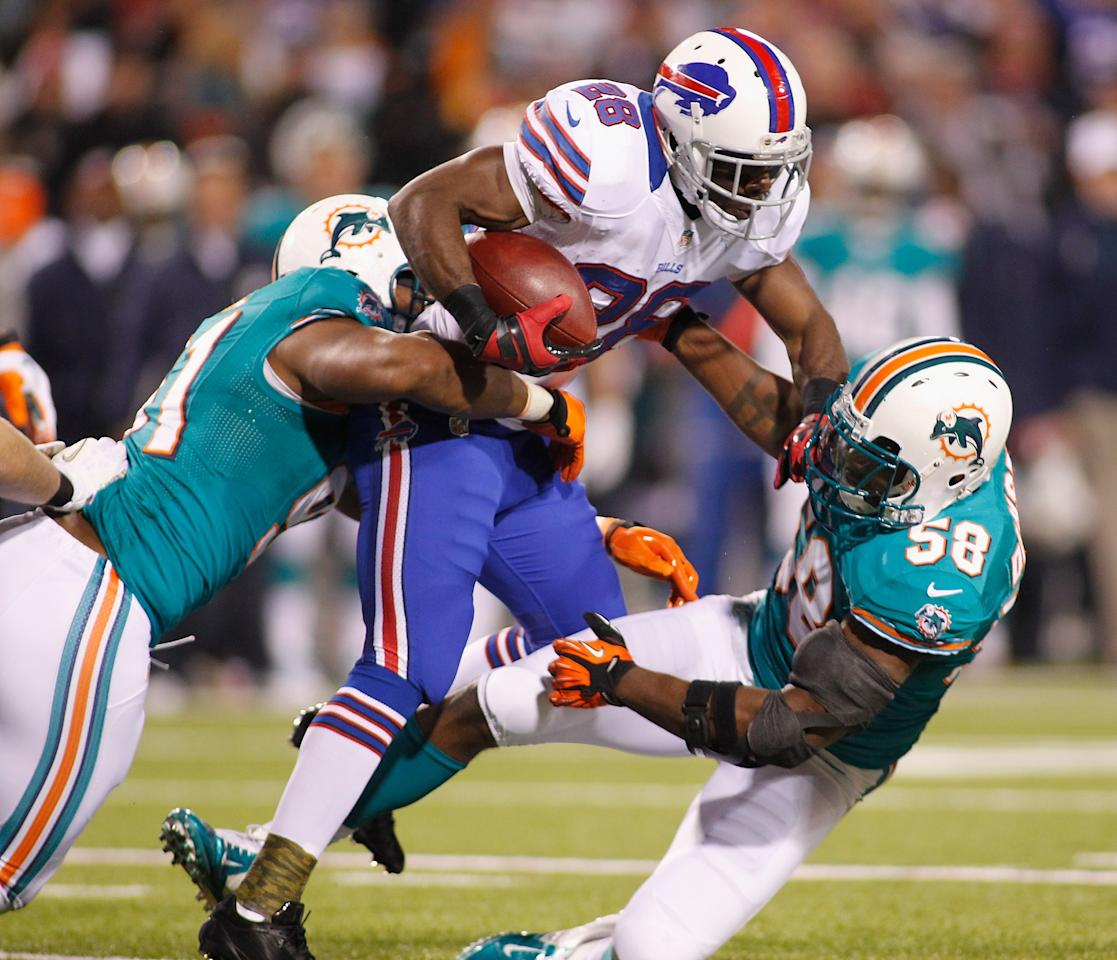 ORCHARD PARK, NY - NOVEMBER 15: C.J. Spiller #28 of the Buffalo Bills runs against  Cameron Wake #91 and  Karlos Dansby #58 of the Miami Dolphins  at Ralph Wilson Stadium on November 15, 2012 in Orchard Park, New York.  (Photo by Rick Stewart/Getty Images)