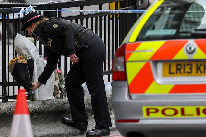 <p>A police officer lays a bunch of flowers at a tribute near the London Bridge area of London Sunday, June 4, 2017. (Photo: Luke MacGregor/Bloomberg via Getty Images) </p>