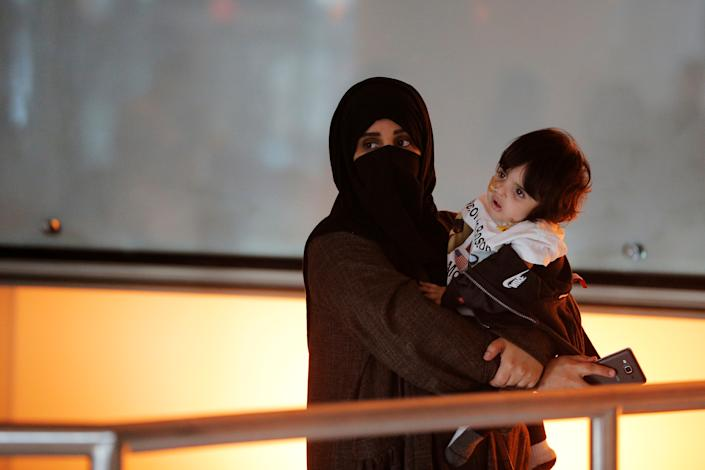 A woman and her daughter wait for a flight from Qatar