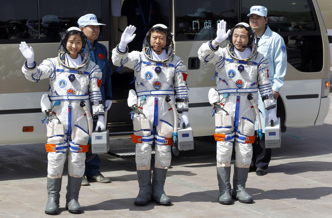 China's astronauts from left., Liu Yang, Liu Wang, and Jing Haipeng wave before they depart for the Shenzhou 9 spacecraft rocket launch pad at the Jiuquan Satellite Launch Center in Jiuquan, China, Saturday, June 16, 2012. China will send its first woman and two other astronauts into space Saturday to work on a temporary space station for about a week, in a key step toward becoming only the third nation to set up a permanent base in orbit.(AP Photo/Ng Han Guan)