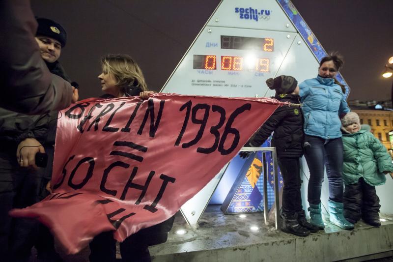 "A gay rights activist holds a banner in front of a large clock showing the number of days left until the start of the Olympic games as police officers approach, left, in St. Petersburg, Russia, Wednesday, Feb. 5, 2014. Russian gay rights activists protested the upcoming Olympic Games in Sochi. Two activists unfurled banners reading ""Berlin 1936 = Sochi 2014,"" referring to the Olympic Games that were held in the capital of Nazi Germany. One-man pickets are legal in Russia and the two activists holding signs were spaced far enough apart that neither was arrested. (AP Photo/Elena Ignatyeva)"