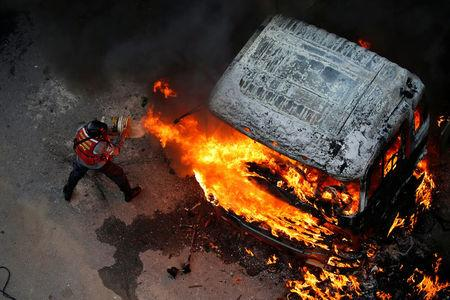 A fireman tries to extinguish a fire during a rally against Venezuela's President Nicolas Maduro in Caracas