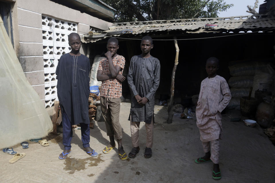 Bello Ibrahim, left, Habubakar Liti, centre, Isah Nasir, third left and Usman Mohammad Rabiu, recently released students, inside their family house in Ketare, Nigeria, Saturday Dec. 19, 2020. Nigeria's freed schoolboys have reunited with their joyful parents after being held captive for nearly a week by gunmen allied with jihadist rebels in the country's northwest. Relieved parents hugged their sons tightly on Saturday in Kankara, where more than 340 boys were abducted from the Government Science Secondary school on the night of Dec. 11. (AP Photo/Sunday Alamba)