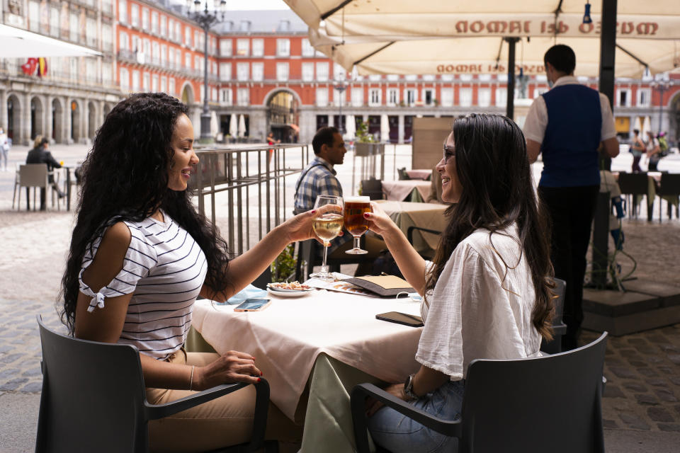 Customers sit at tables socially distanced from each other at the outdoor terrace of a bar, operating at reduced capacity in Plaza Mayor  to open after 9 weeks of severe lockdown by Covid-19 on May 26, 2020 in Madrid, Spain. The regions of Madrid as well as the metropolitan area of Barcelona entered Phase 1, which allows sidewalk cafes to reopen at 50% capacity  (Photo by Oscar Gonzalez/NurPhoto via Getty Images)