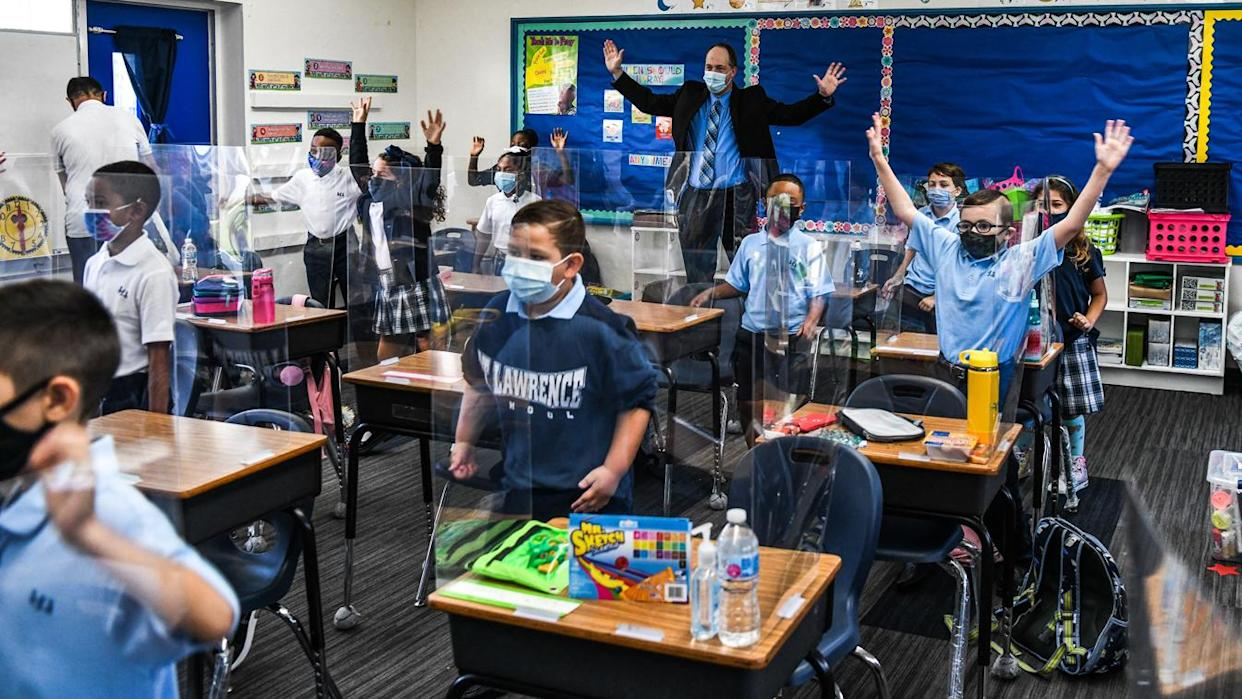 The new Superintendent of Schools for the Archdiocese of Miami, Jim Rigg (back of class), dances with students wearing masks on the first day in school at the St. Lawrence Catholic School, on Aug. 18, 2021.