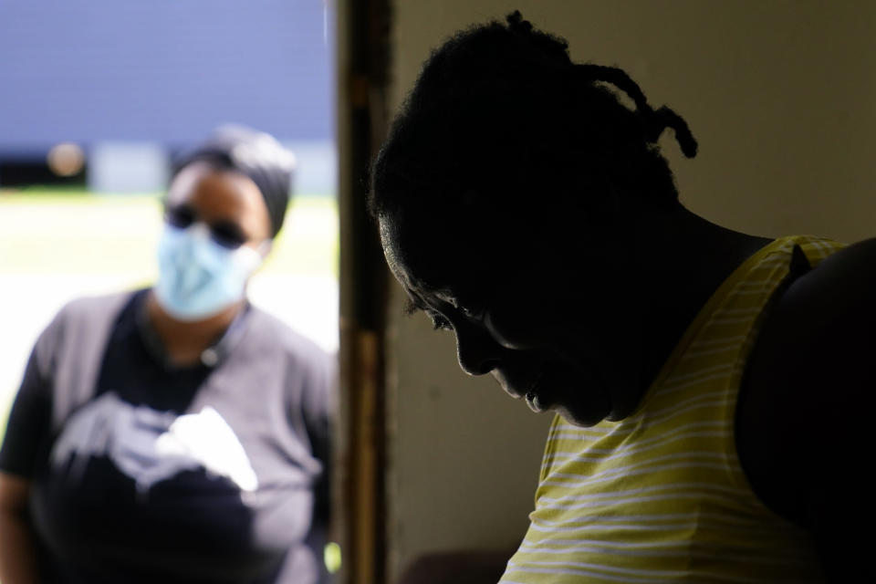 In the aftermath of Hurricane Ida, Lationa Kemp, 57, pauses while talking with Andreanecia Morris, background left, a housing advocate, Saturday, Sept. 4, 2021, in the Lower Ninth Ward of New Orleans. (AP Photo/Matt Slocum)
