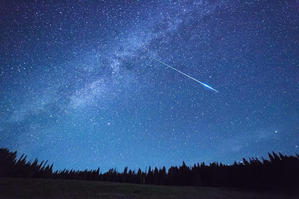 A meteor streaks over Yellowstone Park.