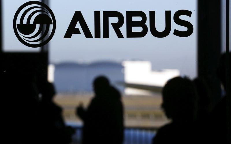 People are silhouetted past a logo of the Airbus Group during the Airbus annual news conference in Colomiers