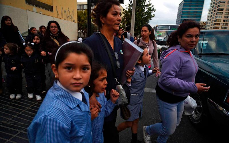 Women and schoolchildren evacuate a building during a 7.1 magnitude quake in Vina del Mar, Chile on Monday - Credit: AFP
