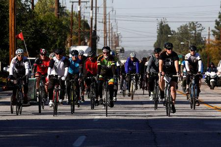 San Bernardino Police Department Sgt. Emil Kokesh, center left, leads cyclists and law enforcement officers down East San Bernardino Avenue, the location of the final shootout with suspects, during the San Bernardino Police Department IRC Memorial Bike Ride on the one year anniversary of the San Bernardino attack in San Bernardino, California, U.S. December 2, 2016.  REUTERS/Patrick T. Fallon