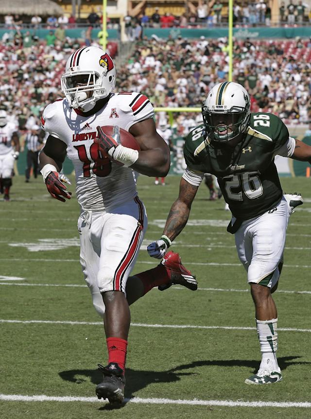 Louisville tight end Gerald Christian (18) beats South Florida safety Mark Joyce (26) on a 69-yard touchdown reception during the second quarter of an NCAA college football game Saturday, Oct. 26, 2013, in Tampa, Fla. (AP Photo/Chris O'Meara)