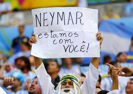 """A fan holds up a sign reading,"""" Neymar. We are with you."""" before the 2014 World Cup quarter-finals between Argentina and Belgium at the Brasilia national stadium in Brasilia July 5, 2014. REUTERS/Dominic Ebenbichler"""