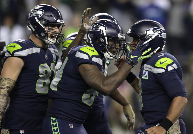 Seattle Seahawks tight end Ed Dickson, center, celebrates with quarterback Russell Wilson, right, and tight end Nick Vannett, left, after Dickson caught a pass from Wilson for a touchdown against the Green Bay Packers during the second half of an NFL football game Thursday, Nov. 15, 2018, in Seattle. (AP Photo/Stephen Brashear)