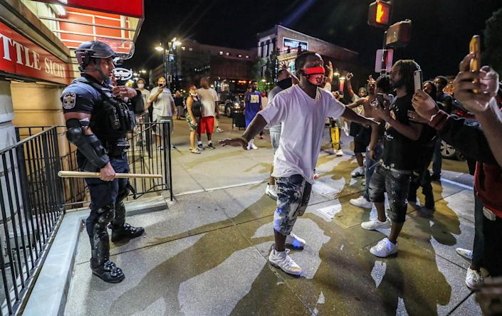 Protesters surround Louisville Metro Police Department officer Galen Hinshaw in front of Bearno's restaurant on Thursday, May 28, 2020 in Louisville, Kentucky. Five strangers linked arms to keep the crowd from getting to Hinshaw.