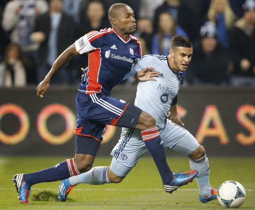 New England Revolution defender Jose Goncalves (23) and Sporting Kansas City forward Dom Dwyer (14) tangle during the first half of an MLS playoff soccer match in Kansas City, Kan., Wednesday, Nov. 6, 2013. (AP Photo/Orlin Wagner)