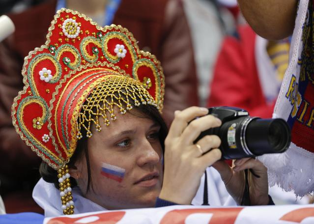 A hockey fan rooting for Russia takes photos during the second period of a men's ice hockey game against Slovenia at the 2014 Winter Olympics, Thursday, Feb. 13, 2014, in Sochi, Russia. (AP Photo/Julio Cortez)