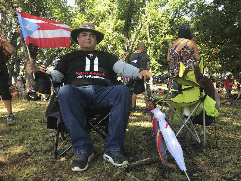 "Jose Troche, a 64-year-old doctor from Yauco, sits under the shade in a beach chair as he waits for the protest march to demand the resignation of Governor Ricardo Rossello, to begin in San Juan, Puerto Rico, Monday, July 22, 2019. ""This right now is a dream,"" he said as he gestured toward the massive crowd. ""The people are united."" Troche believes Puerto Rico is at a crossroads, and that the upheaval will force people to be more conscious about who they vote into office next year. (AP Photo/Danica Coto)"