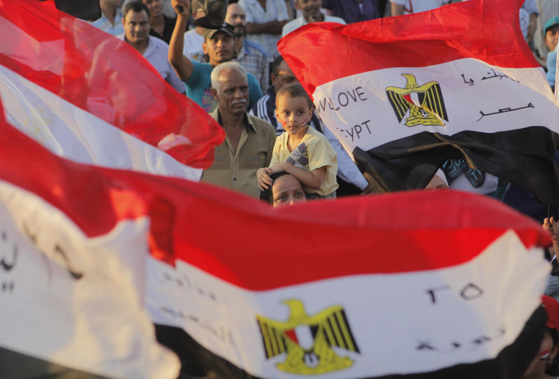 Egyptian supporters of the Supreme Council of Armed Forces (SCAF) shout anti-Muslim Brotherhood slogans and wave national flags during a protest to dissolve the religious political party at the memorial of the Unknown Soldier in Cairo, Egypt, Friday, July 6, 2012. (AP Photo/Amr Nabil)
