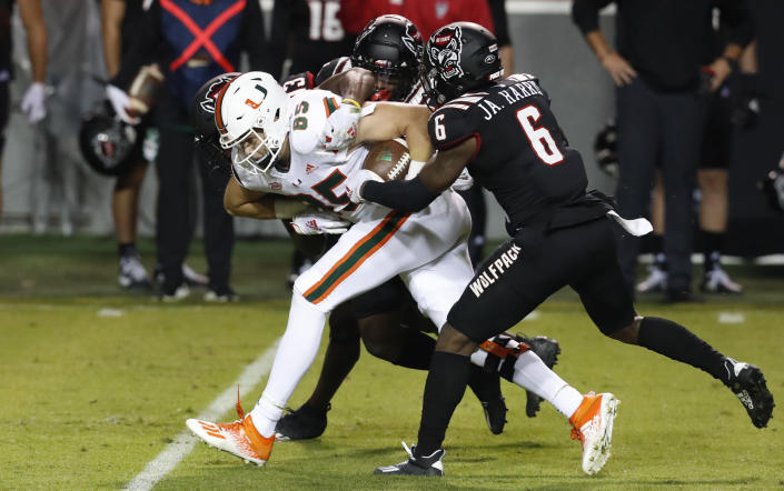 Miami tight end Will Mallory (85) is tackled by North Carolina State's Jakeen Harris (6), Tyler Baker-Williams (13) and Cecil Powell (4) during the first half of an NCAA college football game Friday, Nov. 6, 2020, in Raleigh, N.C. (Ethan Hyman/The News & Observer via AP, Pool)