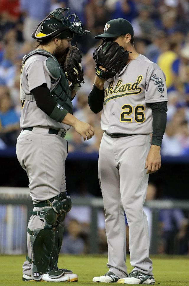 Oakland Athletics starting pitcher Scott Kazmir and catcher Derek Norris meet on the mound during the fifth inning of a baseball game against the Kansas City Royals Wednesday, Aug. 13, 2014, in Kansas City, Mo. (AP Photo/Charlie Riedel)