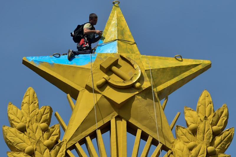 A worker repaints a star yellow at the top of a Stalin-era skyscraper in Moscow blue, on August 20, 2014. The star was painted in yellow and blue, the Ukrainian national colors, by unknown people