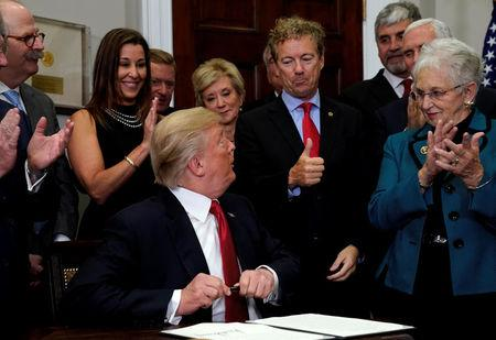 REFILE - CORRECTING TYPO Senator Rand Paul (R-KY) gives U.S. President Donald Trump a thumbs up after Trump signed an Executive Order to make it easier for Americans to buy bare-bone health insurance plans and circumvent Obamacare rules at the White House in Washington, U.S., October 12, 2017. REUTERS/Kevin Lamarque