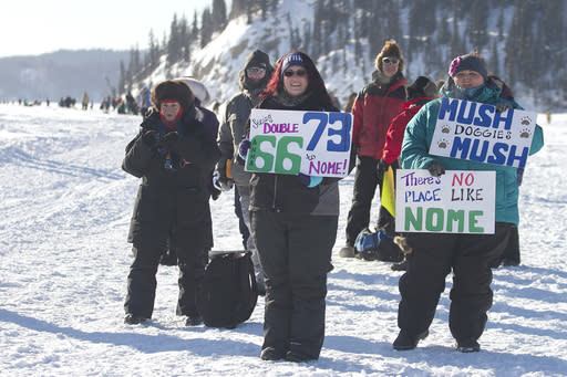 FILE - In this March 6, 2017, file photo, Melissa, center, and Sarah, right, Burnett, both of Fairbanks, hoist handmade signs for passing Iditarod mushers on the Chena River in Fairbanks, Alaska. The women are avid race fans, following the mushers' GPS trackers obsessively and staying as up-to-date as possible with all race news. Technology has increasingly made the 47-year-old race more immediate to fans and safer for competitors, said Chas St. George, acting CEO of the Iditarod Trail Committee, the races governing board. (AP Photo/Ellamarie Quimby, File)