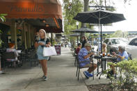 Patrons dine at a restaurant Friday, Oct. 2, 2020, in Winter Park, Fla. In his drive to return the state to normalcy, Republican Gov. Ron DeSantis lifted limits on indoor seating at restaurants, saying they can operate at 100% in municipalities with no restrictions and that other local governments can't restrict indoor seating by more than 50%. (AP Photo/John Raoux)