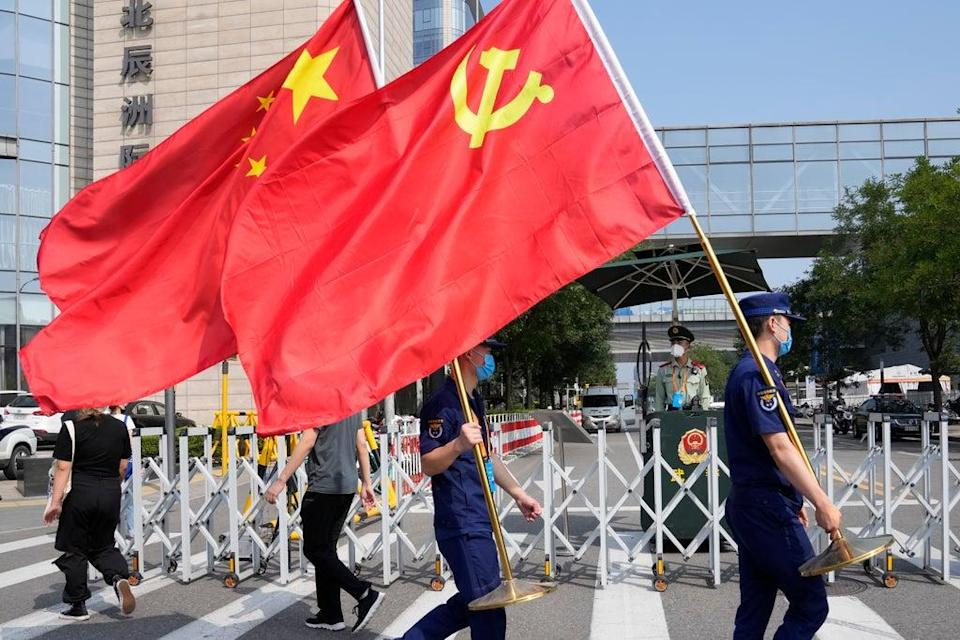 File. Security personnel holding the Communist Party and Chinese national flags prepare to enter the venue for the China International Fair for Trade in Services in Beijing on China on 2 September 2021   (Associated Press)