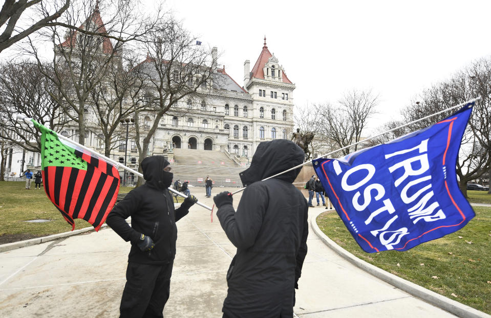 """A supporter from Black Liberation left, and one from the group """"All Of Us' hold flags while counter-protesting a Trump rally ahead of the inauguration of President-elect Joe Biden and Vice President-elect Kamala Harris at the New York State Capitol Sunday, Jan. 17, 2021, in Albany, N.Y. (AP Photo/Hans Pennink)"""