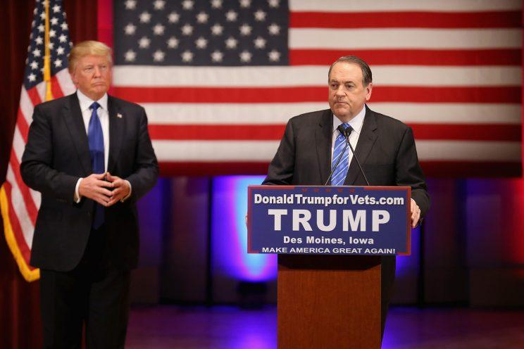 Republican presidential candidate Donald Trump listens as then-fellow candidate Mike Huckabee speaks to veterans at Drake University in Des Moines, Iowa on January 28, 2016.(Photo: Christopher Furlong/Getty Images)
