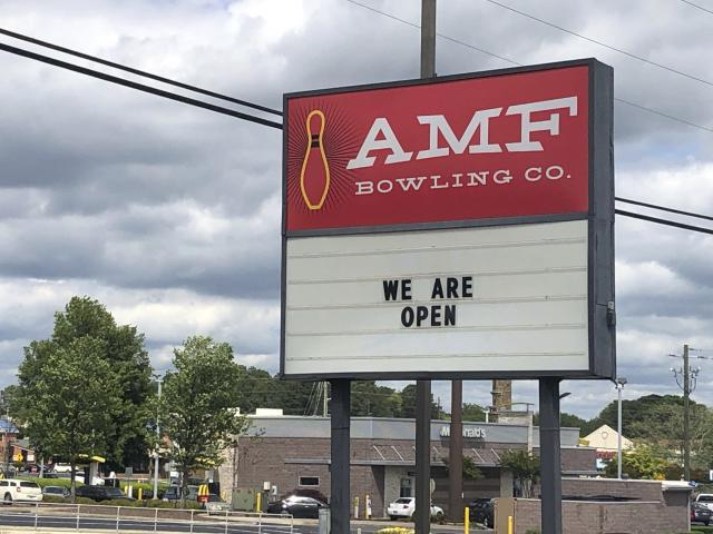 The sign outside the AMF bowling alley in Conyers, Ga., displays a message Friday, April 24, 2020, in Conyers, Ga. Like many industries in America and around the world, bowling has taken a huge financial blow because of lockdown measures meant to contain the highly contagious coronavirus. (AP Photo/Paul Newberry)