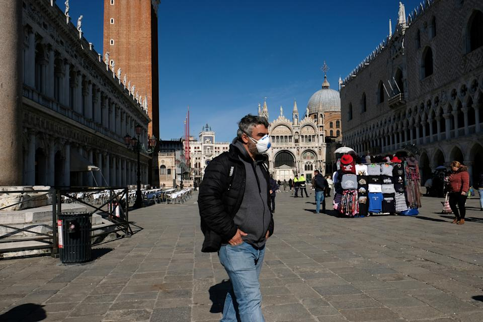 A man wearing a protective mask walks through an empty Saint Mark's Square in Venice as Italy battles a coronavirus outbreak, Venice, Italy, February 27, 2020. REUTERS/Manuel Silvestri