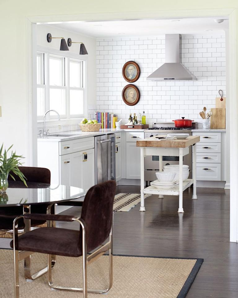 "<p>An industrial table is the perfect makeshift island for a farmhouse kitchen. In this one designed by <a href=""https://www.alexandermreid.com/"" target=""_blank"">Alexander Reid</a>, the subway tiles brighten up the whole room and the black sconces sharpen up the airy aesthetic and the stainless steel appliances are undeniably modern. </p>"