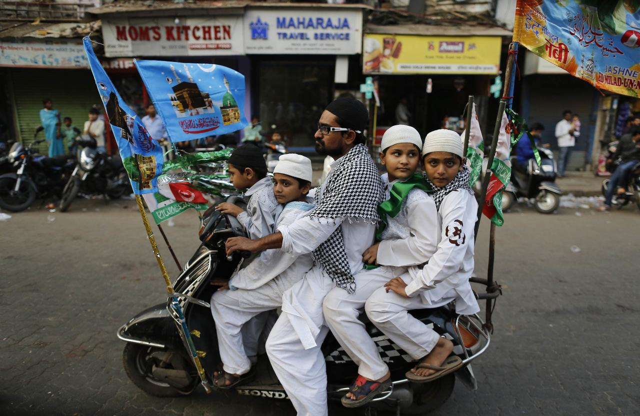 Muslims ride on a scooter on their way to participate in a procession to mark Eid-e-Milad-ul-Nabi, or birthday celebrations of Prophet Mohammad in Mumbai