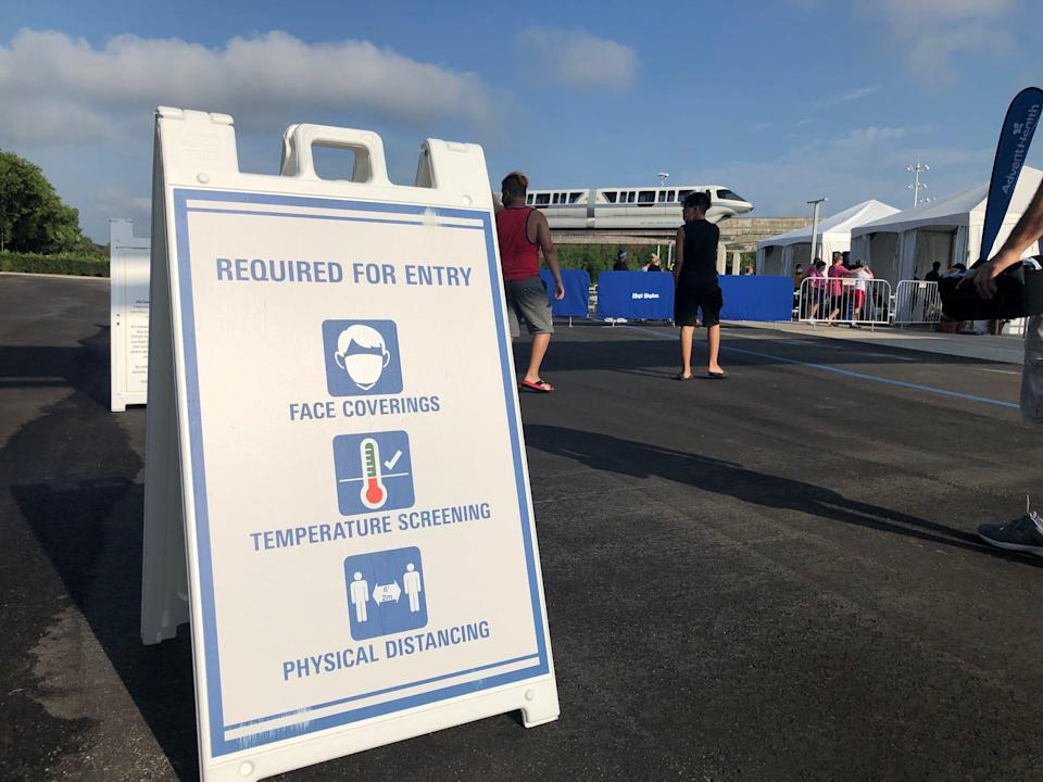 A sign in the Disney parking lot warned visitors that face coverings, temperature screenings and social distancing would be required for admission.