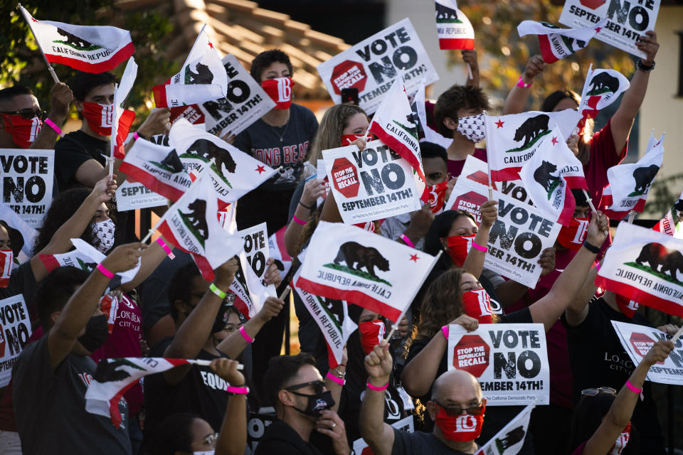 Supporters of California Gov. Gavin Newsom wave signs and California flags while waiting for the arrival of the governor and President Joe Biden at a rally Monday, Sept. 13, 2021, in Long Beach, Calif. (AP Photo/Jae C. Hong)