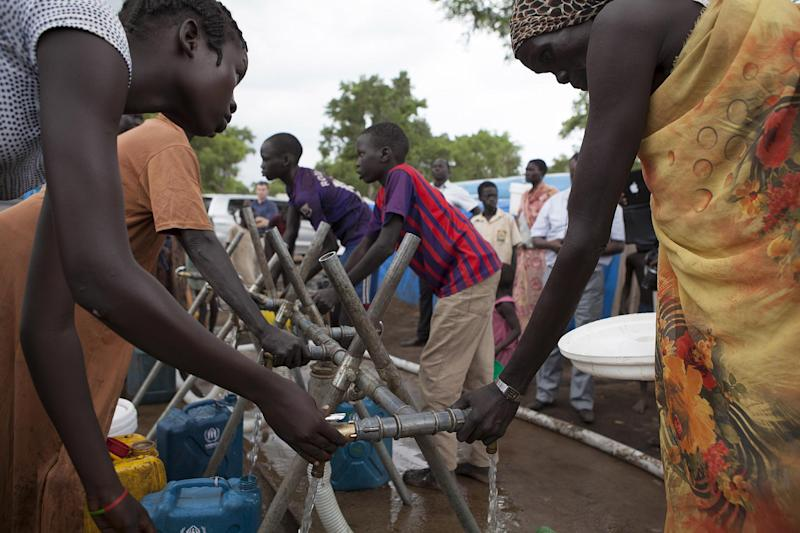South Sudanese refugees fetch water at a watering point in a camp for Internally Displaced People in Gambella, Ethiopia, on July 10, 2014