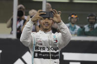 Mercedes driver Lewis Hamilton of Britain uses his mobile phone as he celebrates pole position during the qualifying session at the Yas Marina racetrack in Abu Dhabi, United Arab Emirates, Saturday, Nov. 30, 2019. The Emirates Formula One Grand Prix will take place on Sunday. (AP Photo/Hassan Ammar)