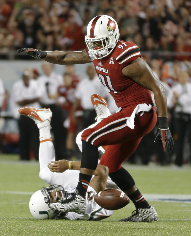 Miami quarterback Stephen Morris, lower left, fumbles the ball as he is hit by Louisville defensive end Marcus Smith (91) during the first half of the Russell Athletic Bowl NCAA college football game in Orlando, Fla., Saturday, Dec. 28, 2013. Louisville recovered the ball. (AP Photo/John Raoux)