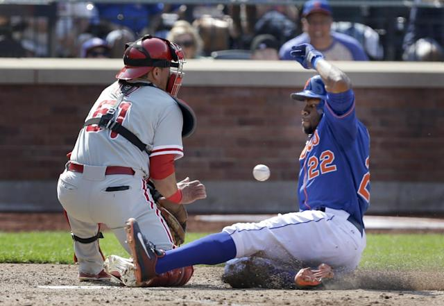 New York Mets' Eric Young Jr., right, slides safely home before the ball reaches Philadelphia Phillies catcher Carlos Ruiz during the sixth inning of the baseball game at Citi Field Thursday, Aug. 29, 2013 in New York. (AP Photo/Seth Wenig)