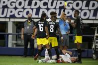 Jamaica midfielder Daniel Johnson (16) and Oniel Fisher (8) look on as Damion Lowe (17) receives a yellow card from referee Cesar Ramos after knocking down United States defender Sam Vines, on ground, in the second half of a CONCACAF Gold Cup quarterfinals soccer match, Sunday, July 25, 2021, in Arlington, Texas. (AP Photo/Brandon Wade)