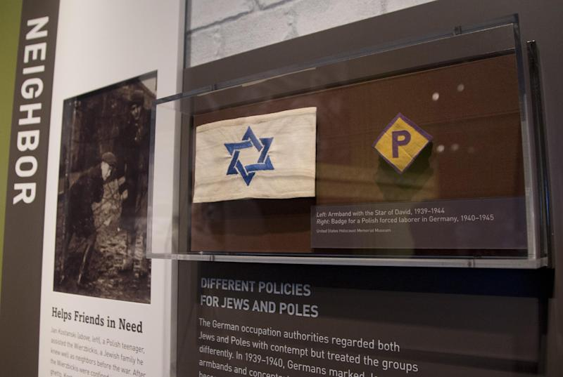 "This Thursday, April 25, 2013 photo shows an armband with the Star of David and a badge for a forced laborer in Germany at the United States Holocaust Memorial Museum during a preview of the new exhibit ""Some Were Neighbors: Collaboration & Complicity in the Holocaust"" in Washington. The exhibition, opening April 30, 2013, includes interviews with perpetrators of collaboration and complicity in the Nazi genocide. (AP Photo/Carolyn Kaster)"