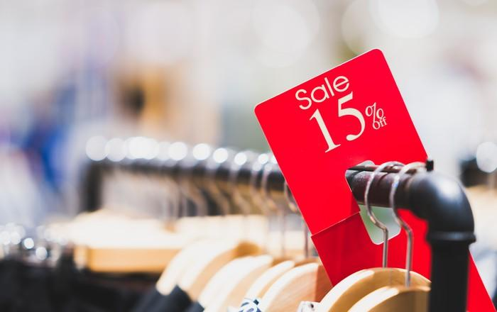 15 percent off tag on a clothing sale rack.