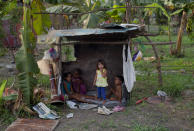 """In this April 8, 2013 photo, children look out from their playhouse in a squatter settlement near Tacarigua, Venezuela. Outside Venezuela's capital, power outages, food shortages and unfinished projects abound; important factors heading into Sunday's election to replace Venezuela's late President Hugo Chavez, who died last month after a long battle with cancer. An estimated 2 million of the country's nearly 30 million people lack permanent homes, and one of Chavez's anti-poverty """"missions"""" builds them. But it's been slow going. The government says it has built 370,500 homes and apartments over the past two years, and more than 3 million people applied for them. (AP Photo/Ramon Espinosa)"""