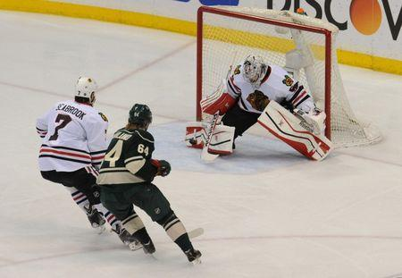 May 13, 2014; Saint Paul, MN, USA; Chicago Blackhawks goalie Corey Crawford (50) makes a save as defenseman Brent Seabrook (7) and Minnesota Wild center Mikael Granlund (64) look for a rebound during overtime of game six of the second round of the 2014 Stanley Cup Playoffs at Xcel Energy Center. The Blackhawks clinch the second round with a 2-1 victory over the Wild in overtime. Mandatory Credit: Marilyn Indahl-USA TODAY Sports