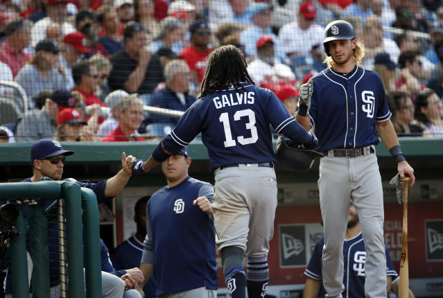 San Diego Padres' Freddy Galvis (13) celebrates scoring with Travis Jankowski, right, and others during the fifth inning of a baseball game against the Washington Nationals at Nationals Park, Wednesday, May 23, 2018, in Washington. (AP Photo/Alex Brandon)