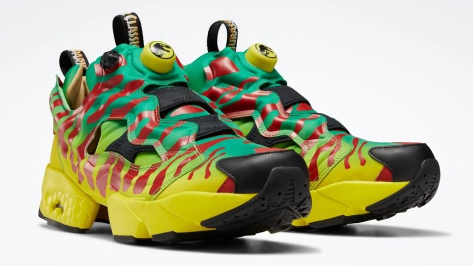 A pair of Jurassic Park Reebok sneakers designed to look like the park's truck, with yellow, red striped, and green
